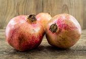 Pomegranate isolated on wooden background — Stock Photo