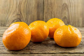 Ripe tangerines on wooden background — Photo