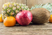 Delicious and arranged tropical fruit in the wooden background — Stock Photo