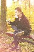 Young attractive man in a black jacket in autumn park — Stock Photo