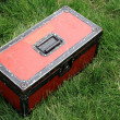 Red tin box on a green lawn — Stock Photo