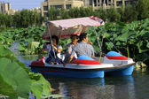 Pleasure boat driving slowly in the water, in a park — Stock Photo