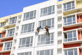 Painter in high rise buildings — Stock Photo