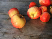 Red apples on a wooden surface in the autumn evening — Stock Photo