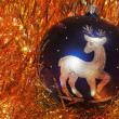 Blue Christmas tree decoration with silver figure deer on red-golden tinsel — Stock Photo