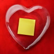 Yellow note inside glass heart with red background — Stock Photo