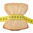 Piece of bread grasped by measuring tape — Photo