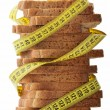 Bread with measure tape indicating weight loss — Stok fotoğraf