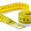 Whirled yellow tape measure — Stock fotografie
