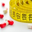 Diet pills and measuring tape — Stock Photo