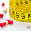 Stock Photo: Diet pills and measuring tape