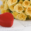 Yellow roses and a box holding wedding rings with musical background — Stock Photo