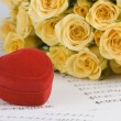 Yellow roses and a box holding wedding rings with musical background — Stock Photo #28218491