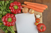 Grocery shopping list with notebook and fresh vegetables — Stock Photo