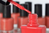 Close-up of a bottle of red nail polish with other bottles in background — Stock Photo