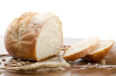 Loaf of bread, partly sliced — Stock Photo