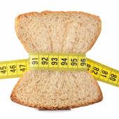 Morceau de pain, saisi par le ruban à mesurer — Photo