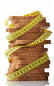 Bread with measure tape indicating weight loss — ストック写真