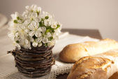 Rustic setting with spring flowers and homemade bread — Stock Photo