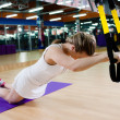 Woman does suspension training with fitness straps — Stockfoto