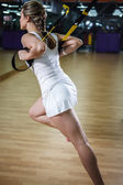 Young fit woman does suspension training — Stock Photo