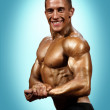 Male bodybuilder against blue background — Stok fotoğraf