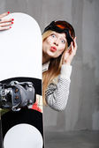 Teenager girl posing in the studio against concrete wall with snowboard — Stock Photo