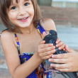 Happy 4 year old girl holding a bird in her hands — Stock Photo