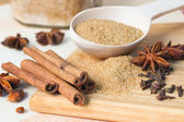 Brown sugar, cinnamon sticks, star aniseed and cloves — Stock Photo