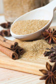 Brown sugar in wooden spoon with cinnamon, star anise and cloves — Foto Stock