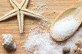 Sea salt crystals in wooden spoon with sea shells and starfish on wooden background — Stock Photo