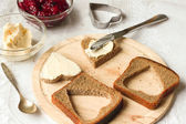Hearts from bread with butter, knife, jam and wooden board — Stock fotografie