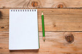 Notebook with green pencil on wooden table — Stock Photo