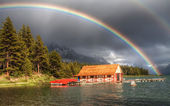 House on the lake in nature with a splendid rainbow — Stock Photo