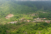 A town surrounded with forest on a mountain slope  — Stock Photo