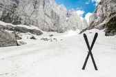 Alpine valley with a pair of crossed skis  — Stock Photo