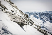 Steep mountain slope with frozen rocks and ridge in the back — Stock fotografie
