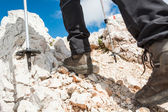 Close up of hiking shoes and trekking poles — Stock Photo