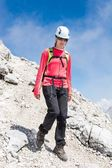 Female climber descending a mountain trail — Stock Photo