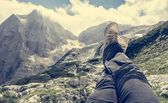 Pair of leggs stretched into the air with a mountain view — Stock Photo