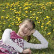 Girl in the flowering meadow laughing — Stock Photo
