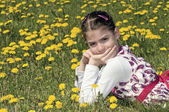Girl in the flowering meadow looking at camera — Stock Photo