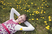 Girl in the flowering meadow on her back — Stock Photo