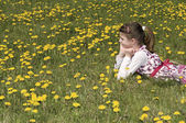 Girl in the flowering meadow looking far — Stock Photo