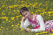 Girl in the flowering meadow smiling — Stock Photo