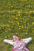 Girl in the flowering meadow resting — Stock Photo