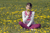 Girl in the flowering meadow smelling — Stock Photo
