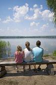 Kids sitting on the lakeside — Stock Photo