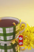 Large tea mug with yellow flower close — Photo