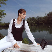 A woman with laptop in park — Stock Photo